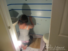 """Taping horizontal lines 8"""" apart for our stripes in the downstairs 1/2 bath"""
