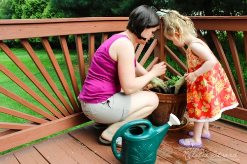 Vivian and I took a quick few minutes to plant a tomato in a pot on the porch before we headed to small group this evening.  Vivian helped me to move the soil around the plant and water it.